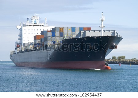 A loaded container ship coming into Fremantle Port in Western Australia. All insignia and logos have been removed. - stock photo