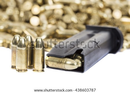 A loaded gun clip with a pile of bullets in the background - stock photo