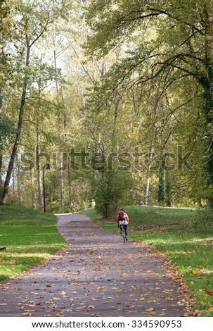 A lone bicycle rider disappears down the bike trail at Alton Baker Park in Eugene Oregon. - stock photo