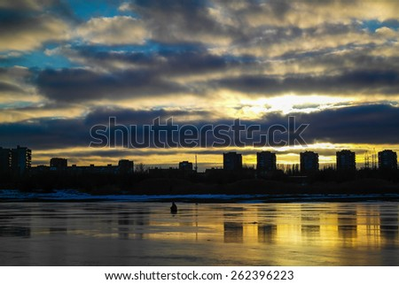 a lone fisherman on the ice of the Bay at sunset - stock photo