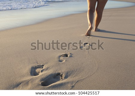 A lone girl walks along the waterline of a white sand beach - stock photo