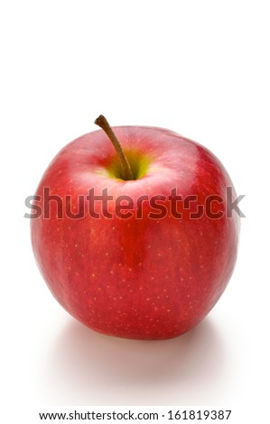 A lone juicy red apple sitting on a white table. - stock photo