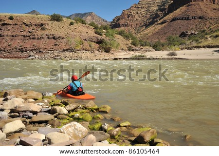 A lone kayaker paddling with canyon walls in the background. - stock photo
