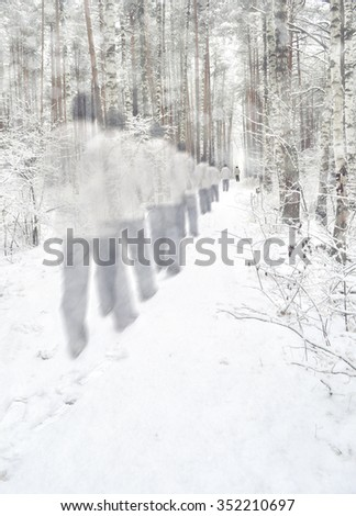 A lone man and his phantoms on the road in the winter forest. - stock photo