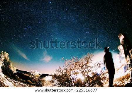 A lone person looking towards lit up buildings. - stock photo