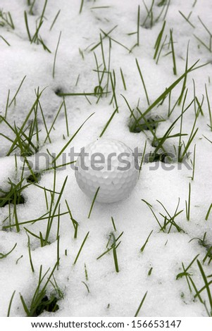 a lone single golf ball in the snow covered grass in Ireland at winter - stock photo