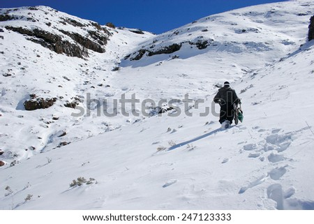 A lone snowboarder begins the hike up a mountain in search of fresh powder in the Maluti Mountains in Lesotho. - stock photo