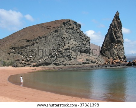 A lone traveler walks among the spectacular lava formations on a deserted beach in the Galapagos. - stock photo