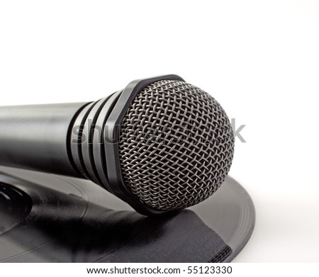 A lonely black microphone over a vinyl record - stock photo