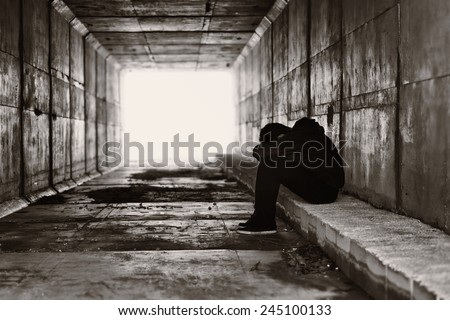 A lonely boy sits on a curb on the right side of a tunnel - stock photo