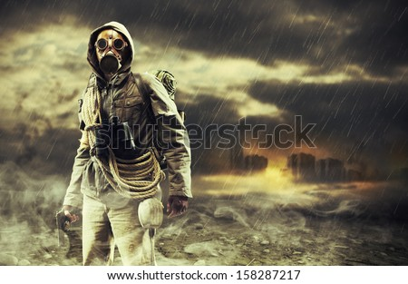 A lonely hero wearing gas mask, city destroyed on the background - stock photo