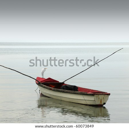 A lonely rowboat on calm seas against moody grey sky - stock photo