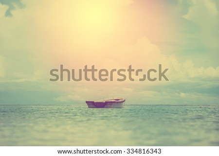 A lonely small boat floating in beautiful tropical ocean, Thailand. Vintage filter. - stock photo