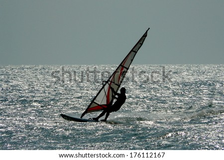 A lonely windsurfer riding the sea during a wonderful sunset in Jericoacoara's main beach, Brazil  - stock photo
