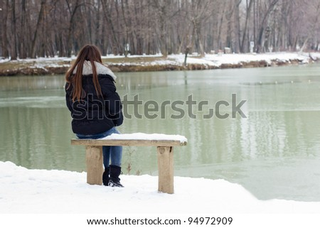 A lonely young woman sitting on a bench beside the lake, winter time. - stock photo