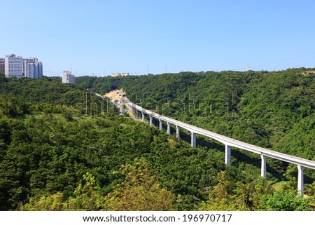 A long bridge nestled between hills covered in green trees. - stock photo