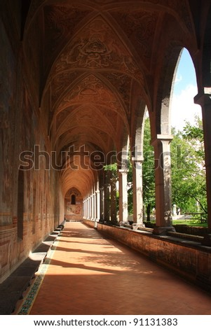 A long cloister in a catholic cathedral with a series of columns - stock photo
