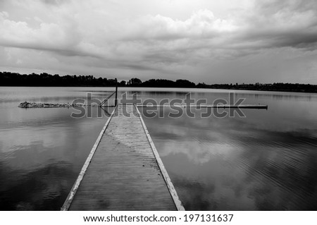 A long dock leading out into a very calm lake. - stock photo