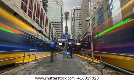 A Long Exposure Evening Shot of Lightrail Subway Trains Arriving and Departing from a Downtown Station - stock photo