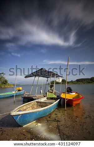 A long exposure image of fisherman boats parked at a lakeside of Tasoh Lake located in Perlis, Malaysia - stock photo
