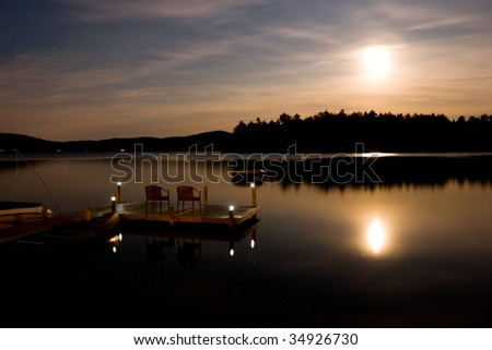 A long exposure of moonlight illuminating a calm flat lake, island and dock. - stock photo