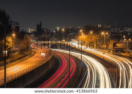 A long exposure of traffic on a motorway, with city lights and a church visible on the skyline - stock photo