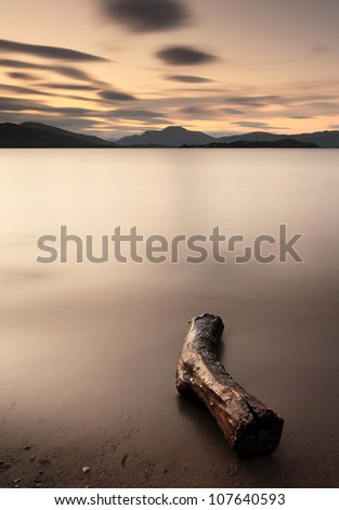 A long exposure taken on the shores of Loch Lomond with a log in the foreground and Ben Lomond and surrounding mountains in the distance. - stock photo