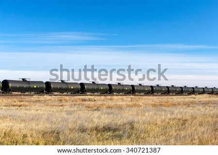 A long line of DOT-111 tank cars, commonly used in North America to transport crude oil to refineries along the coasts. - stock photo