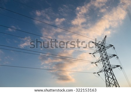 A long line of electrical transmission towers (electricity pylons) carrying high voltage lines in the city at sunset. - stock photo