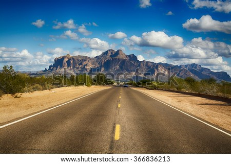 A long remote road leading to the base of famous Superstition Mountain in Arizona shows the beauty of this desert landscape. - stock photo