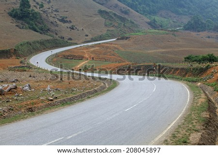 """A long road shaped """"S"""" passing through a mountain area. Abstract meaning of reaching long term propose. - stock photo"""