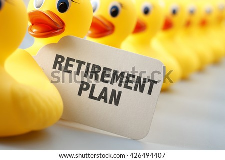 A long row of yellow rubber ducks with a sign that says Retirement Plan on it.  - stock photo