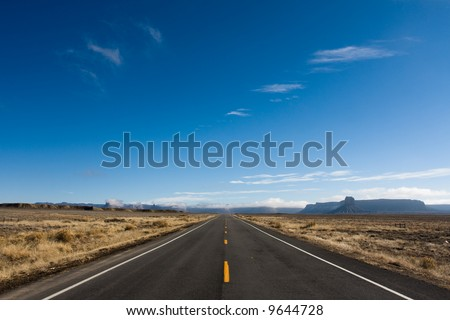 A long straight road transverses the border between New Mexico and Colorado - stock photo