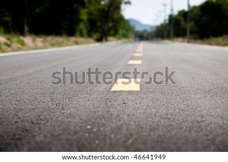 A long stretch of road with dividing line - stock photo