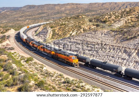 A long train loaded with double-stack white cargo containers winds its way around tight s-curves in mountain countryside. All ID marks removed. A line of tanker cars waiting. California, near I-15. - stock photo