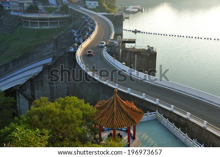 A long, winding highway between a gazebo and waterway. - stock photo