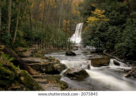 A look downstream from a beautiful  waterfall deep in the forests of Virginia. Fall colors along the stream add to the beauty of the scene. - stock photo