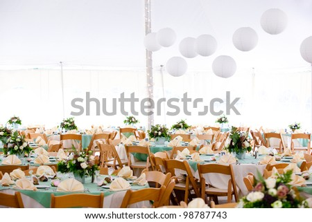 A look inside a tent set for fine dining during a wedding or other catered event - stock photo