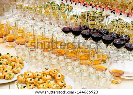 a lot of alcohol drinks on buffet table, catering - stock photo
