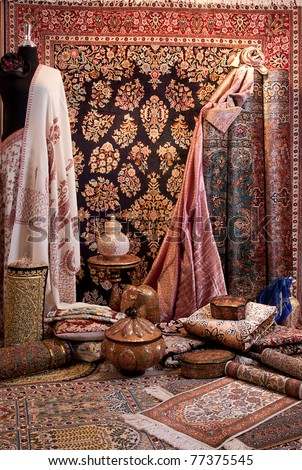 A lot of carpets and clothes shown in carpet shop - stock photo
