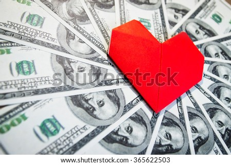 A lot of cash US dollars and a paper heart - stock photo