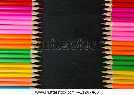 a lot of colored pencils lying on each side closeup on wooden background - stock photo