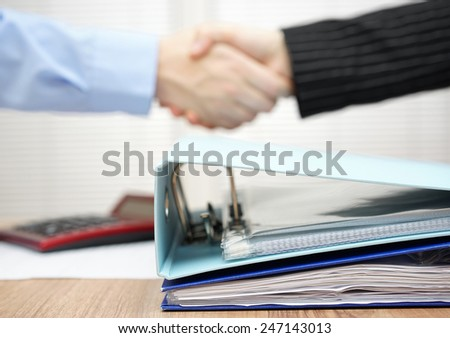 a lot of documentation in binder with  handshake in blur - stock photo