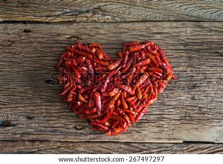 A Lot of dried chili arranged in a heart shape as a food background. Hot love concept - stock photo