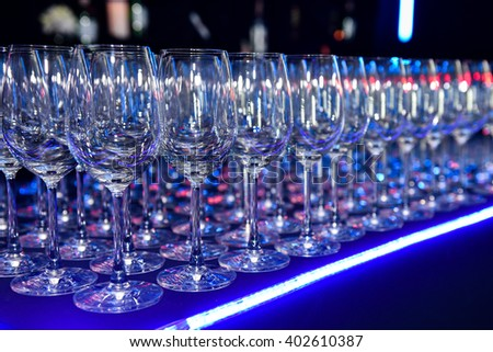 a lot of empty clean wine glasses on a dark background in Blue light at night club - stock photo