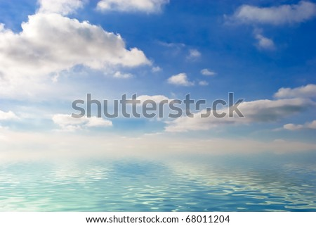 a lot of fluffy clouds on blue sky over big water - stock photo