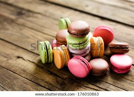 A lot of french colorful macarons on a woody floor - stock photo