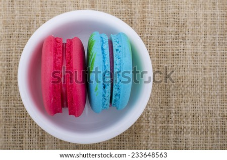 A lot of french colorful macarons shape on a woody floor in vintage tone style,macarons in a cup - stock photo
