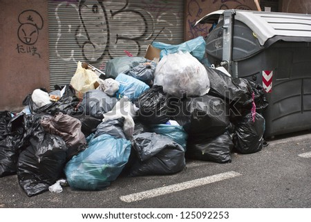 a lot of garbage in the street and container - stock photo