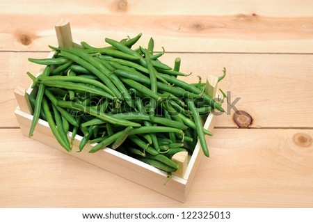 a lot of green beans in wooden case - stock photo